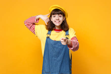 Girl teenager in french beret doing phone gesture like says call me back, pointing index finger on camera isolated on yellow background. People sincere emotions, lifestyle concept. Mock up copy space Stock Photo