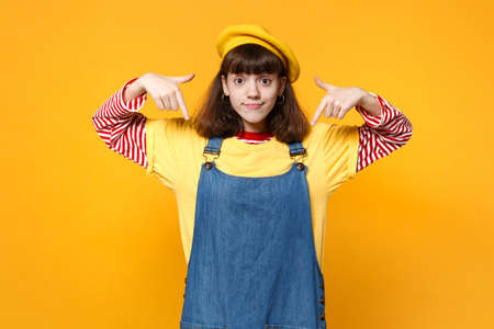 Portrait of smiling girl teenager in french beret, denim sundress pointing index fingers down isolated on yellow background in studio. People sincere emotions, lifestyle concept. Mock up copy space Stock fotó
