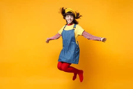 Portrait of smiling cute girl teenager in french beret and denim sundress jumping with flowing hair isolated on yellow wall background in studio. People emotions lifestyle concept. Mock up copy space