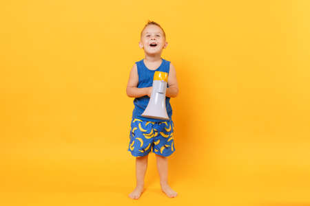Kid boy 3-4 years old in blue beach summer clothes hold speak in megaphone isolated on bright yellow orange background children studio portrait. People childhood lifestyle concept Mock up copy space