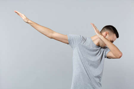 Portrait of cheerful young man in casual clothes showing dab dance gesture isolated on grey wall background in studio. People sincere emotions, lifestyle concept. Mock up copy space. Advertising area