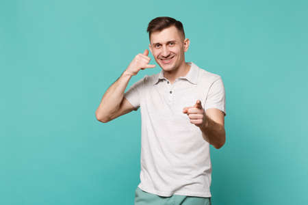 Young man in casual clothes pointing finger on camera, doing phone gesture like says call me back isolated on blue turquoise background. People sincere emotions, lifestyle concept. Mock up copy space Stock fotó