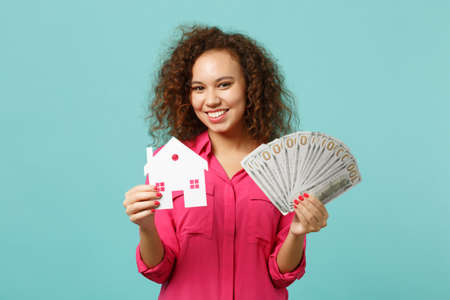 Smiling african girl in casual clothes holding paper house, fan of money in dollar banknotes, cash money isolated on blue turquoise background. People emotions, lifestyle concept. Mock up copy space