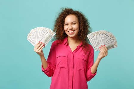 Smiling african girl in casual clothes holding fan of money in dollar banknotes, cash money isolated on blue turquoise wall background. People sincere emotions, lifestyle concept. Mock up copy space