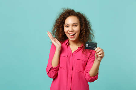 Portrait of cheerful african girl in pink casual clothes holding credit bank card isolated on blue turquoise wall background in studio. People sincere emotions, lifestyle concept. Mock up copy space