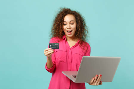 Excited african girl in casual clothes using laptop pc computer holding credit bank card isolated on blue turquoise background in studio. People sincere emotions lifestyle concept. Mock up copy space