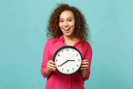 Portrait of surprised african girl in pink casual clothes holding round clock isolated on blue turquoise wall background in studio. People sincere emotions, lifestyle concept. Mock up copy space 版權商用圖片