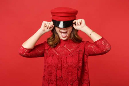 Portrait of excited young woman in lace dress covering eyes with cap keeping mouth open isolated on bright red wall background in studio. People sincere emotions lifestyle concept. Mock up copy space 写真素材