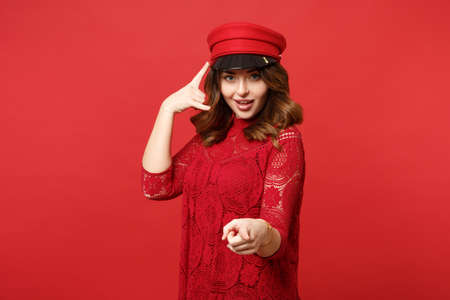 Beautiful woman in lace dress cap doing phone gesture like says call me back pointing index finger on camera isolated on red background. People sincere emotions, lifestyle concept. Mock up copy space
