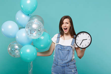 Nervous screaming young woman in denim clothes holding round clock while celebrating with colorful air balloons isolated on blue turquoise background. Birthday holiday party, people emotions concept