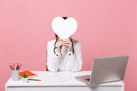 Female doctor sit at desk work on computer with medical document hold heart in hospital isolated on pastel pink wall background. Woman in medical gown glasses stethoscope. Healthcare medicine concept 免版税图像
