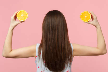Back rear view of young woman in summer clothes holding two halfs of fresh ripe orange fruit isolated on pink pastel wall background. People vivid lifestyle relax vacation concept. Mock up copy space