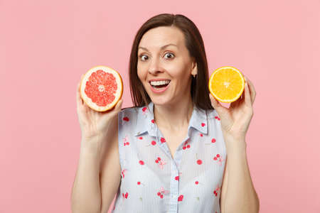 Surprised young woman in summer clothes holding halfs of fresh ripe grapefruit, orange fruit isolated on pink pastel wall background. People vivid lifestyle relax vacation concept. Mock up copy space 版權商用圖片