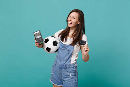 Laughing young woman football fan support favorite team with soccer ball, wireless modern bank payment terminal to process and acquire credit card payments isolated on blue turquoise wall background