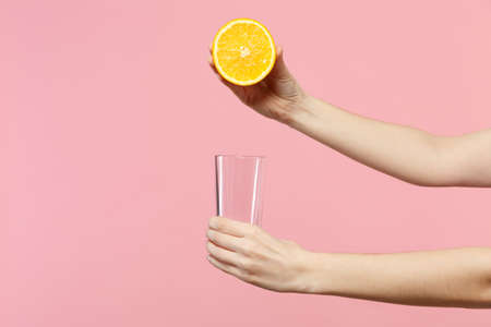 Close up cropped photo of female holding in hands half of fresh ripe orange fruit, glass cup isolated on pink pastel wall background. People vivid lifestyle relax vacation concept. Mock up copy space