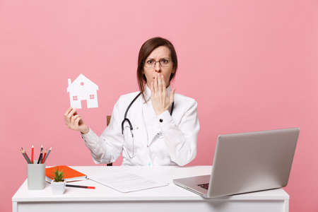 Female doctor sit at desk work on computer with medical document hold house in hospital isolated on pastel pink wall background. Woman in medical gown glasses stethoscope. Healthcare medicine concept
