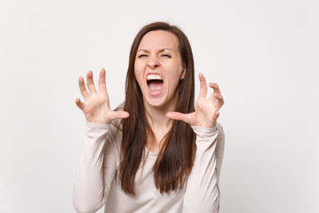 Crazy young woman in light clothes shouting, growling like animal, making cat claws gesture isolated on white wall background in studio. People sincere emotions, lifestyle concept. Mock up copy space