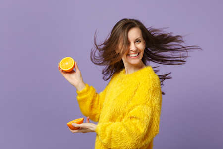 Smiling young woman in fur sweater with fluttering hair hold halfs of fresh ripe orange fruit isolated on violet pastel background. People vivid lifestyle, relax vacation concept. Mock up copy space