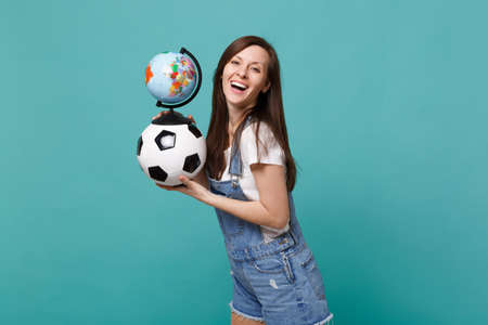 Laughing woman football fan support favorite team with soccer ball Earth world globe isolated on blue turquoise background. People emotions, sport family leisure lifestyle concept. Mock up copy space