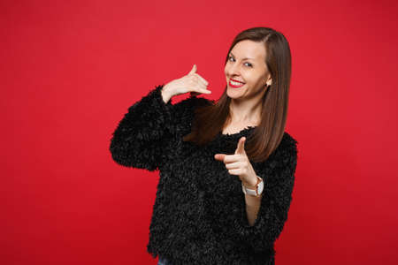 Joyful young woman in fur sweater doing phone gesture like says call me back, pointing index finger on camera isolated on red background. People sincere emotions lifestyle concept. Mock up copy space Stock fotó