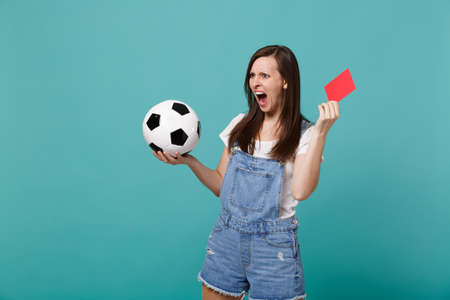 Irritated shocked young girl football fan support team with soccer ball, red card propose player retire from field isolated on blue turquoise background. People emotions, sport family leisure concept