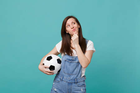Preoccupied young woman football fan support favorite team with soccer ball looking up, put hand prop up on chin isolated on blue turquoise background. People emotions, sport family leisure concept