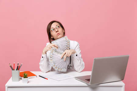 Female doctor sit at desk work on computer with medical document cash money in hospital isolated on pastel pink wall background. Woman in medical gown glasses stethoscope. Healthcare medicine concept