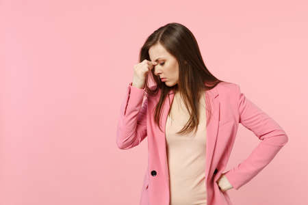 Portrait of tired upset young woman wearing jacket putting hand on nose, keeping eyes closed isolated on pastel pink wall background. People sincere emotions, lifestyle concept. Mock up copy space