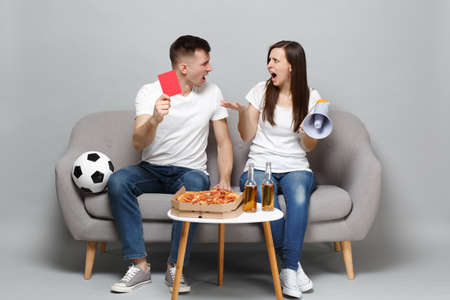 Screaming couple woman man football fans cheer up support favorite team swearing, holding megaphone, red card isolated on grey wall background. People emotions, sport family leisure lifestyle concept