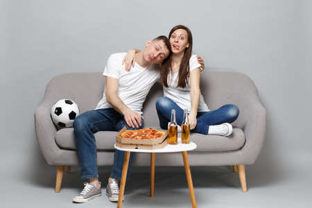 Fun tired couple woman man football fans in white t-shirt cheer up support favorite team sleeping, showing tongue isolated on grey background. People emotions, sport family leisure lifestyle concept