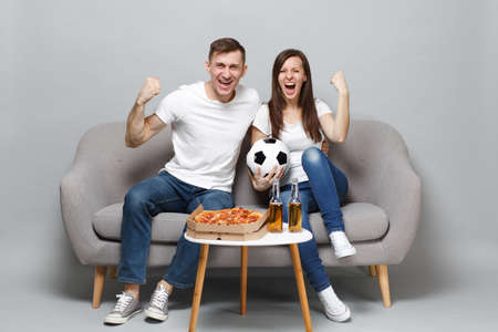 Laughing couple woman man football fans cheer up support favorite team with soccer ball clenching fists like winner isolated on grey background. People emotions sport family leisure lifestyle concept Stock Photo