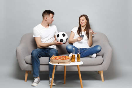 Concerned couple woman man football fans cheer up support favorite team with soccer ball, using mobile phone isolated on grey wall background. People emotions, sport family leisure lifestyle concept Stock Photo