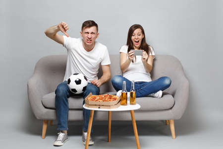 Expressive couple woman man football fans cheer up support favorite team showing thumb down using mobile phone isolated on grey wall background. People emotions sport family leisure lifestyle concept