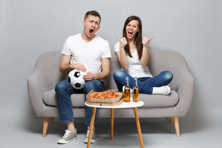 Couple woman man football fans in white t-shirt cheer up support favorite team with soccer ball, showing thumbs up isolated on grey background. People emotions, sport family leisure lifestyle concept