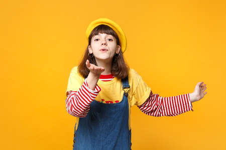 Portrait of ?ute girl teenager in french beret, denim sundress blowing sending air kiss isolated on yellow wall background in studio. People sincere emotions, lifestyle concept. Mock up copy space