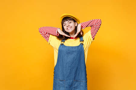 Portrait of charming girl teenager in french beret, denim sundress keeping hands near face isolated on yellow wall background in studio. People sincere emotions, lifestyle concept. Mock up copy space