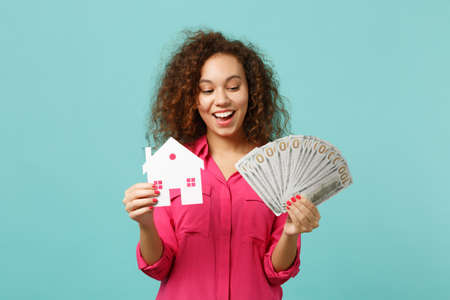 Excited african girl in casual clothes holding paper house, fan of money in dollar banknotes, cash money isolated on blue turquoise background. People emotions, lifestyle concept. Mock up copy space