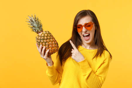 Blinking young woman in heart glasses pointing index finger on fresh ripe pineapple fruit isolated on yellow orange wall background. People vivid lifestyle, relax vacation concept. Mock up copy space
