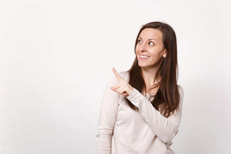 Portrait of smiling young woman in light clothes looking, pointing index finger aside up isolated on white wall background in studio. People sincere emotions, lifestyle concept. Mock up copy space