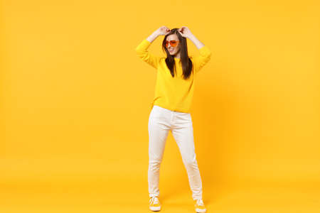 Stunning young woman in casual clothes, heart glasses looking aside, rising hands isolated on yellow orange wall background in studio. People sincere emotions, lifestyle concept. Mock up copy space