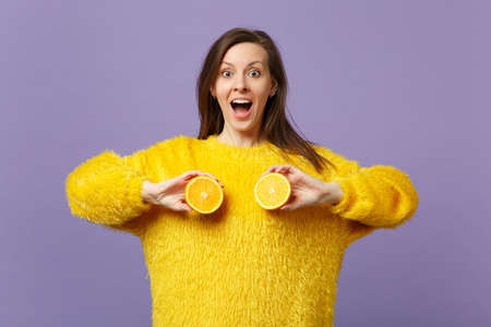 Excited young woman in fur sweater keeping mouth open holding halfs of fresh ripe orange fruit isolated on violet pastel background. People vivid lifestyle, relax vacation concept. Mock up copy space