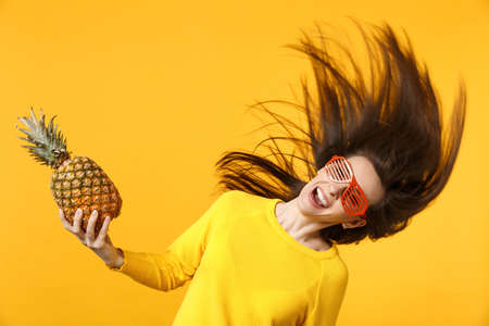 Smiling young woman in funny glasses with flying hair holding fresh ripe pineapple fruit isolated onyellow orange wall background. Peoplevivid lifestyle, relax vacation concept. Mock up copy space