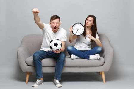 Screaming couple woman man football fans cheer up support favorite team with soccer ball, holding round clock, clenching fist isolated on grey wall background. Sport family leisure lifestyle concept 版權商用圖片