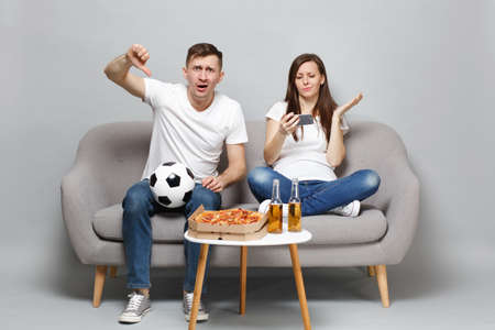Concerned couple woman man football fans cheer up support favorite team showing thumb down using mobile phone isolated on grey wall background. People emotions, sport family leisure lifestyle concept