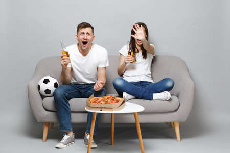 Expressive couple woman man football fans cheer up support favorite team screaming showing stop gesture holding beer bottles isolated on grey background. People emotions, sport family leisure concept