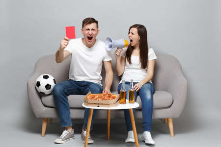 Irritated couple woman man football fans cheer up support favorite team scream on megaphone, holding red card isolated on grey wall background. People emotions, sport family leisure lifestyle concept