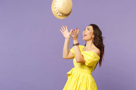 Portrait of cheerful charming young woman in yellow dress throwing up summer hat isolated on pastel violet wall background in studio. People sincere emotions lifestyle concept. Mock up copy space