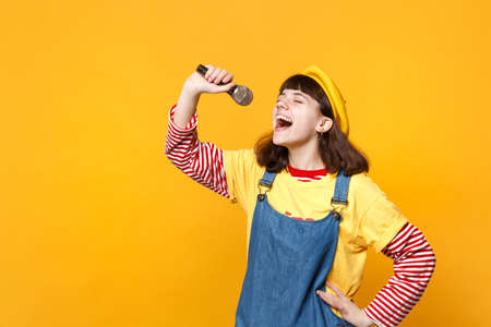 Pretty girl teenager in french beret, denim sundress keeping eyes closed sing song in microphone isolated on yellow background in studio. People sincere emotions lifestyle concept. Mock up copy space