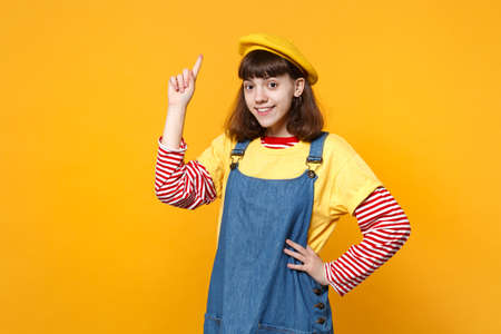 Portrait of smiling girl teenager in french beret, denim sundress pointing index finger up isolated on yellow wall background in studio. People sincere emotions, lifestyle concept. Mock up copy space