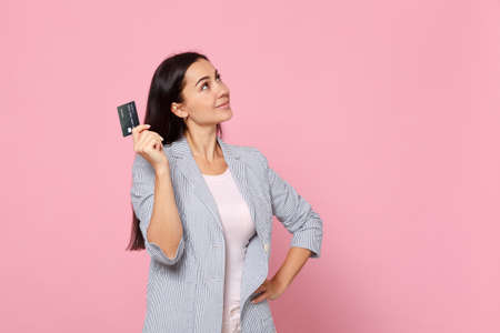 Portrait of pensive young woman in striped jacket looking up holding credit bank card isolated on pink pastel wall background in studio. People sincere emotions, lifestyle concept. Mock up copy space